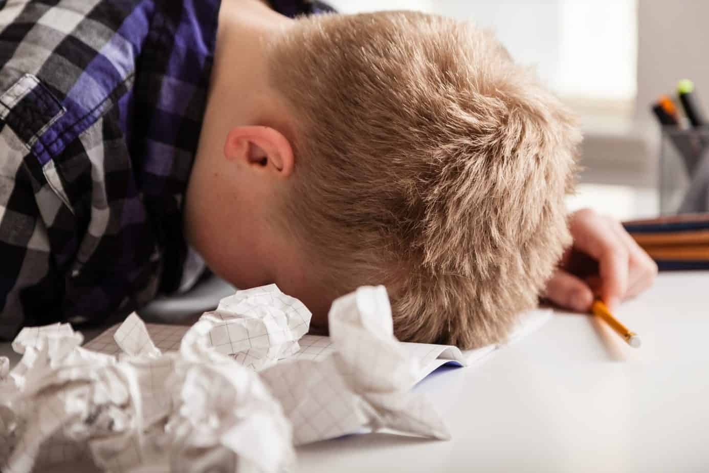 Young boy struggling with his homework sitting with his head down on the table surrounded by crumpled pages of screwed up paper