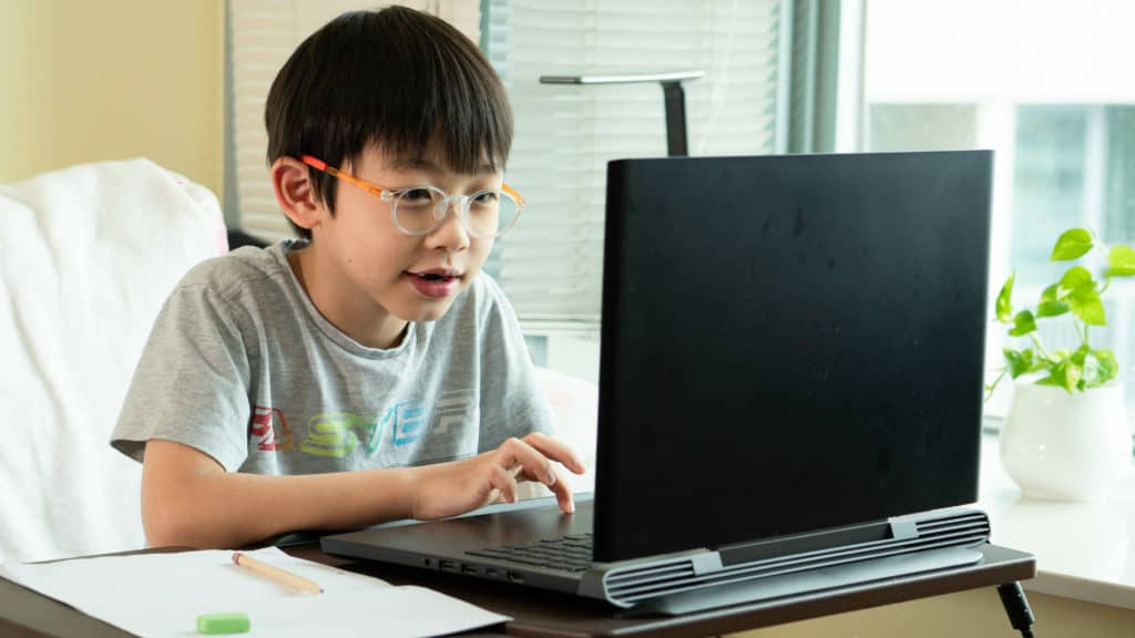 A primary age student playing a math game on a laptop computer. He is having fun and very engaged.